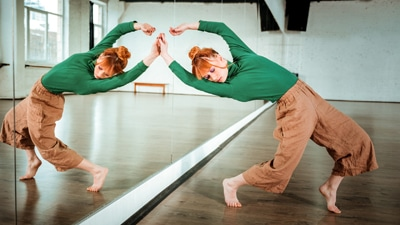 Dancing movements. Professional modern dancer wearing a green turtleneck doing movements near the mirror