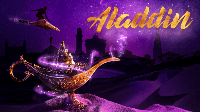 Aladdin Artwork - Aladdin title text in gold with a purple background showing the Colchester skyline, in the top left a silhouette of Aladdin riding a magic carpet and bottom left a genie lamp is resting on some sand with sparkles coming from the top