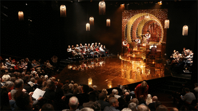 Theatre auditorium, mid-performance, showing audience and performers