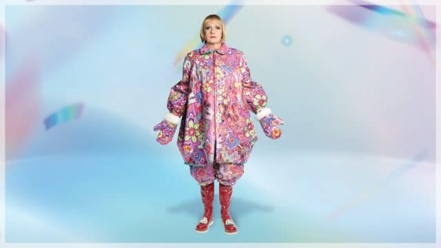 Grayson Perry image - photograph of Grayson in an oversized pink coat on an abstract sky blue background