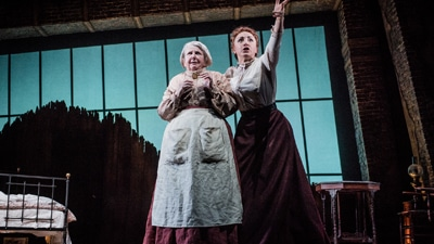 Two actors, mid-performance, one pointing towards the front of the stage