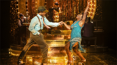 Two actors dancing together on stage