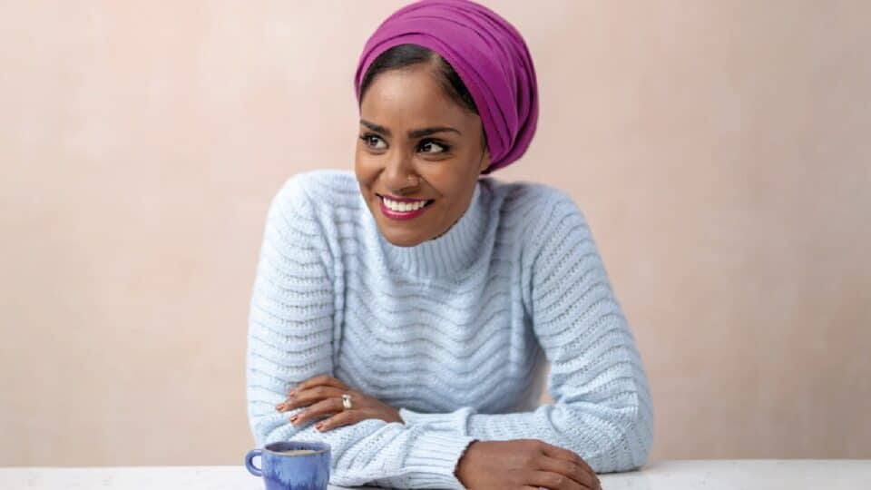 A photograph of Nadiya Hussein leaning forward smiling with her arms crossed, she is wearing a light blue jumper and a purple hair wrap, she is sat down in front of a beige wall with a blue mug on a white table in front of her.