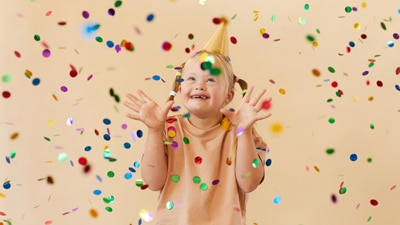 A disabled child wears a party hat and celebrates among confetti.