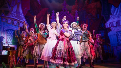 Ten actors in colourful costumes, posed in an arrowhead formation, each raising a fist in the air.