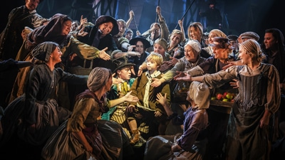 Actors in Victorian era costumes on stage surround a young actor, offering their hands