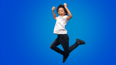 A child dressed in a white shirt and black jeans jumps in front of a blue background.
