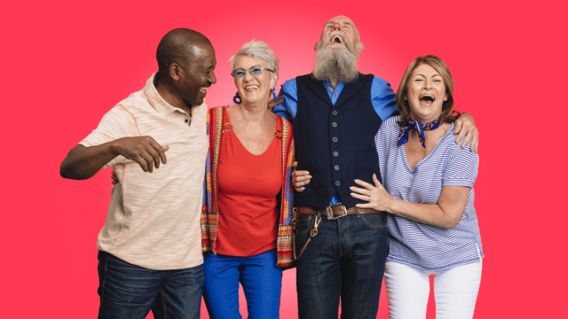 Senior Social Club - group of older people with their arms around each other laughing on a block red background