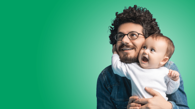 Tots Twinkles - image of a man holding a baby both smiling on a green coloured background