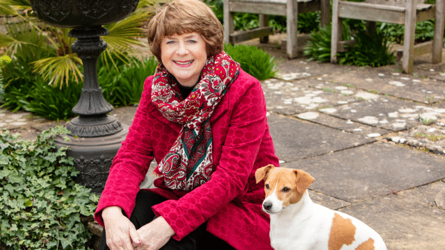 Pam Ayres on outside porch with small dog